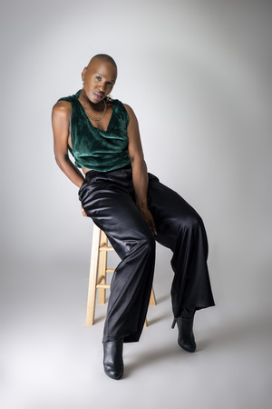 Black African American female fashion model wearing trendy green outfit and heels sitting on a stool.  She is confidently showing off a bold bald hairstyle.   免版税图像
