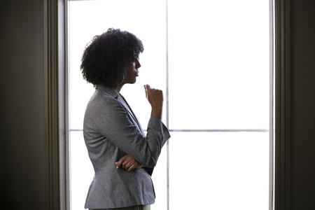 Silhouette di una donna d'affari afroamericana nera stressata che sembra preoccupata e pensa a problemi e fallimenti dalla finestra dell'ufficio. Sembra depressa o sconvolta per debiti o bancarotta.