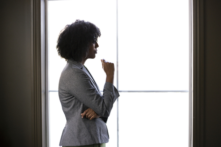 Silhouette of a stressed out black African American businesswoman looking worried and thinking about problems and failure by the office window.  She looks depressed or upset about debt or bankruptcy. Foto de archivo