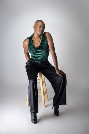 Black African American female fashion model wearing trendy green outfit and heels sitting on a stool.  She is confidently showing off a bold bald hairstyle.   Standard-Bild