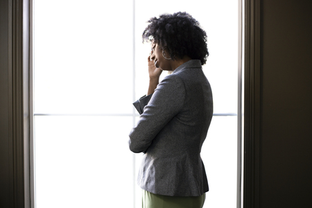 Silhouette of a stressed out black African American businesswoman looking worried and thinking about problems and failure by the office window.  She looks depressed or upset about debt or bankruptcy. 免版税图像