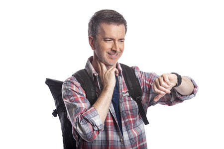 Middle-aged man or senior citizen checking heart rate pulse with health apps on a smartwatch.  He also looks like a hiker checking the wearable technology for gps navigation. Stock Photo