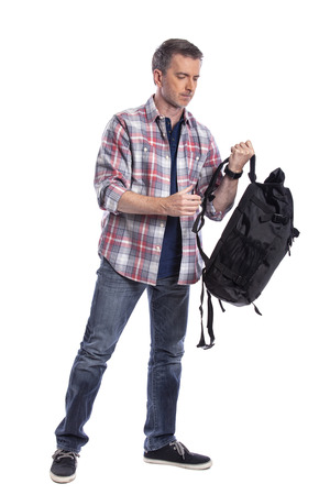 Middle-Aged man preparing a backpack for hiking or trekking.  He could also be a tourist packing hand carry luggage in preparation for a journey.