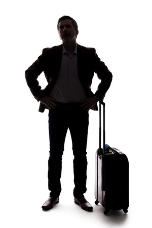 Silhouette of a businessman going on a business trip and traveling with luggage.  The man is carrying bags like preparing to board a flight at an airport. Фото со стока - 124716900