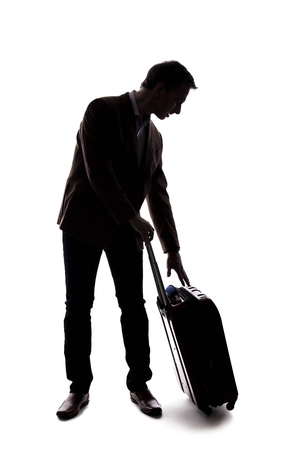 Silhouette of a businessman going on a business trip and traveling with luggage.  The man is carrying bags like preparing to board a flight at an airport. Фото со стока - 124716901