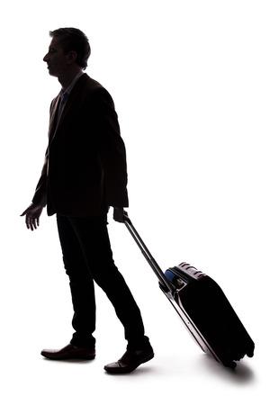 Silhouette of a businessman going on a business trip and traveling with luggage.  The man is carrying bags like preparing to board a flight at an airport. Фото со стока - 124716902