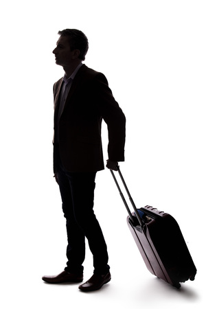 Silhouette of a businessman going on a business trip and traveling with luggage.  The man is carrying bags like preparing to board a flight at an airport. Фото со стока - 124716903