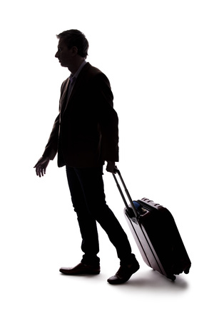 Silhouette of a businessman going on a business trip and traveling with luggage.  The man is carrying bags like preparing to board a flight at an airport. Фото со стока - 124716905