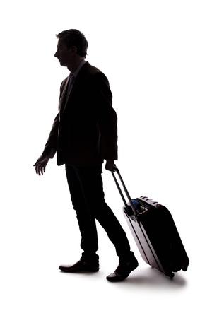 Siluetta di un uomo d'affari che va in viaggio d'affari e viaggia con i bagagli. L'uomo trasporta borse come se si stesse preparando a imbarcarsi su un volo in aeroporto.