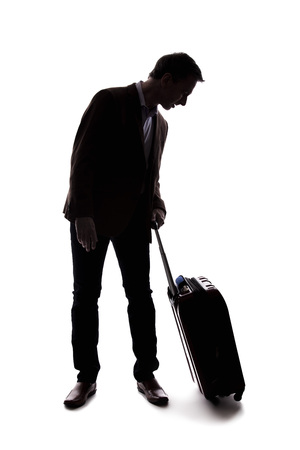 Silhouette of a businessman going on a business trip and traveling with luggage.  The man is carrying bags like preparing to board a flight at an airport.