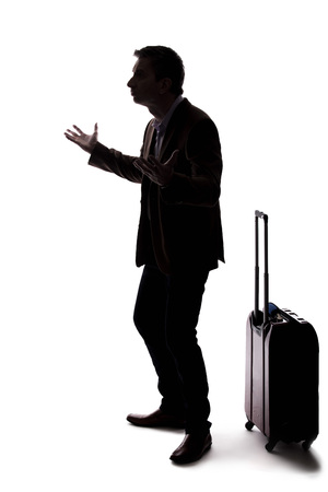 Silhouette of an angry businessman or traveler with luggage as if arguing at an airport about delays or cancellations. The tourist is angry about the stress of travel.