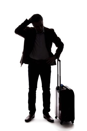 Silhouette of a traveling businessman looking upset because of a delayed or cancelled flight.  The traveler is stressed and waiting with his luggage.  Isolated on a white background.