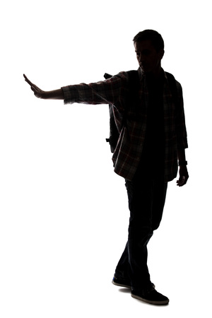 Silhouette of a male tour guide hiking and carrying a backpack on a white background.  He is carefully gesturing stop.  Depicts adventure and exploration.