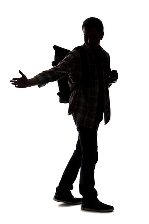 Silhouette of a male tour guide hiking and carrying a backpack on a white background.  He is pointing at something.  Depicts adventure and exploration. Reklamní fotografie