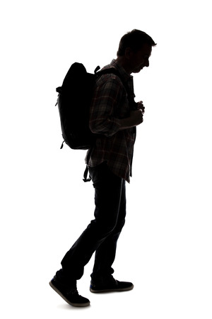 Silhouette of a male tour guide hiking and carrying a backpack on a white background.  The isolated side view man can be used for composites.  Depicts adventure and exploration.