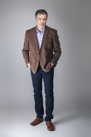 Bearded middle aged fashion model posing with business casual style outfit for mature and confident look.  The trendy brown jacket and jeans and facial hair shows an elegant apparel. 写真素材