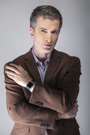 Middle Aged male model wearing a stylish smartwatch for mature fashion.  The wearable technology is used with health apps for fitness tracking.