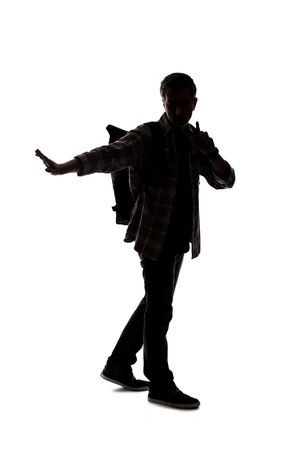 Silhouette of a male tour guide hiking and carrying a backpack on a white background.  He is carefully gesturing stop.  Depicts adventure and exploration. Reklamní fotografie - 124718640