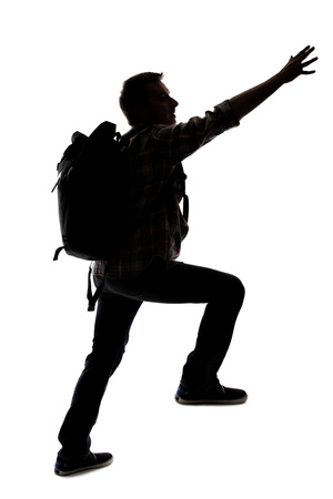 Silhouette of a hiker or mountain climber reaching to move up an imaginary mountain. The image depicts gestures or shape of an active man exploring. Stock Photo