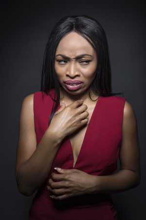 Portrait of a Black African American female wearing a red outfit on a dark background.  She looks disgusted by something gross