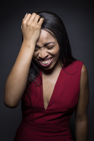 Portrait of a Black African American female wearing a red outfit on a dark background.  She is laughing at a mistake or confused. Reklamní fotografie
