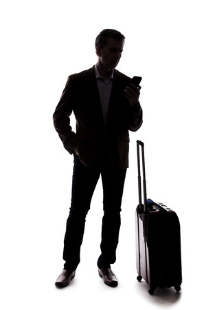 Silhouette of a businessman who is calling for a rideshare with a cellphone.  He is waiting with his luggage as if arriving from an airport.  Isolated on a white background for composites. Banco de Imagens - 124718721