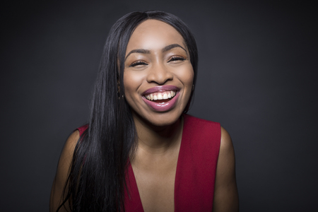 Portrait of a Black African American female wearing a red outfit on a dark background.  She is happy and smiling. Banco de Imagens