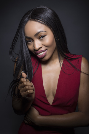 Portrait of a Black African American female wearing a red outfit on a dark background.  She looks shy and embarrassed. Stock Photo