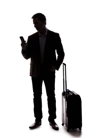 Silhouette of a businessman who is calling for a rideshare with a cellphone.  He is waiting with his luggage as if arriving from an airport.  Isolated on a white background for composites.
