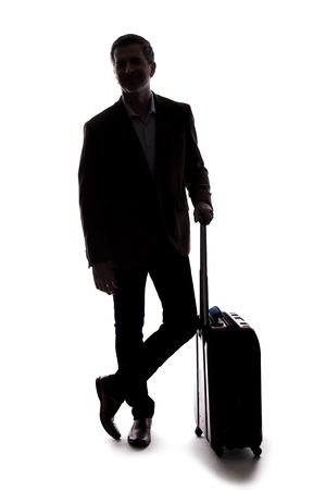Silhouette of a traveling businessman going on a business trip.  He is waiting with luggage as if he is in the airport departure or arrival. Isolated on white background for composites. Reklamní fotografie