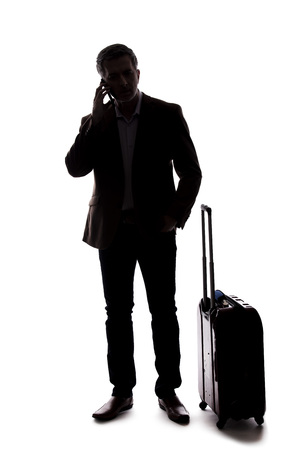 Silhouette of a businessman who is calling for a rideshare with a cellphone.  He is waiting with his luggage as if arriving from an airport.  Isolated on a white background for composites. Banco de Imagens - 124718749
