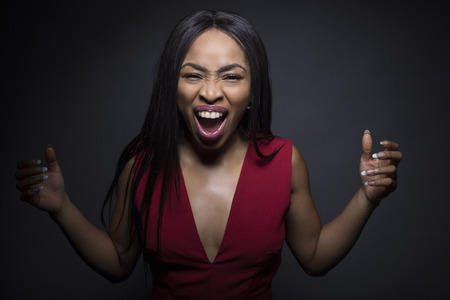 Portrait of a Black African American female wearing a red outfit on a dark background.  She is screaming and looks excited.
