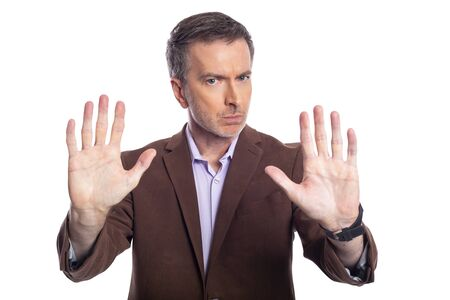 Middle aged bearded businessman on a white background wearing a brown jacket.  The mature man looks like a business executive holding hands up for stop gesture.
