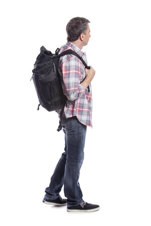 Middle-aged man hiking and carrying a backpack on a white background.  Depicts adventure and exploration.  Isolated for composites.