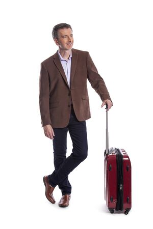 Traveling businessman going on a business trip.  He is waiting with luggage as if he is in the airport departure or arrival. Isolated on white background for composites. Imagens