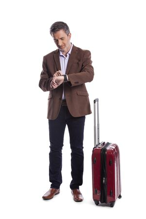 Traveling businessman looking upset because of a delayed or cancelled flight.  The traveler is stressed and waiting with his luggage.  Isolated on a white background.
