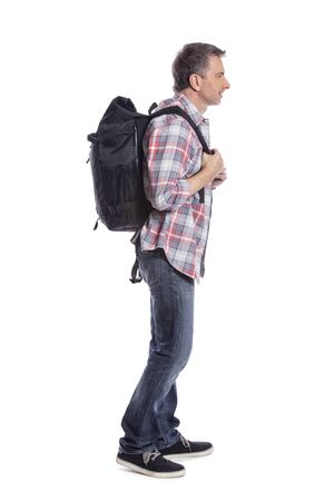 Middle-aged man hiking and carrying a backpack on a white background.  Depicts adventure and exploration.  Isolated for composites. Reklamní fotografie - 124718805