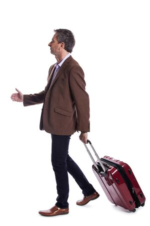 Businessman going on a business trip and traveling with luggage.  The man is carrying bags like preparing to board a flight at an airport. Фото со стока