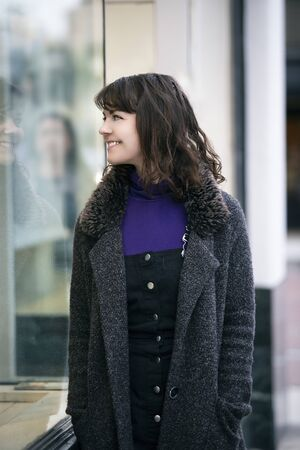 Woman walking outdoors in a city. She is window shopping and looking at a store sale advertising or marketing apparel and clothing on a display glass.
