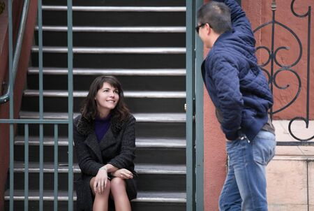 Male flirting with female neighbor sitting on the stairs outside of an apartment complex or condo.  He is confident and charismatic talking to her and depicts dating and relationships.