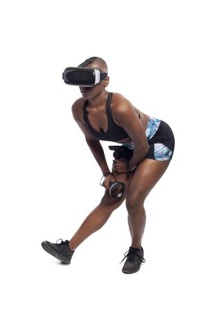 Black female wearing a virtual reality headset and holding wand controllers doing vr fitness exercises. The gamer is in a sports simulation video game for entertainment and healthy physical activity.