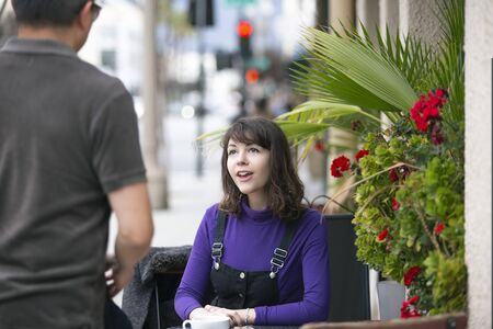 Friends or dating couple meeting and hanging out at an urban city sidewalk cafe.  They are sitting outdoors socializing and talking over coffee or breakfast.
