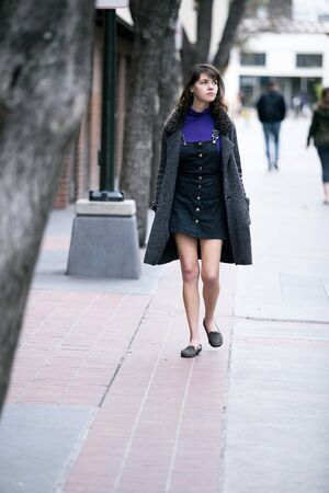 Young pretty woman walking on an urban street sidewalk or a pavement city park.  She looks like an independent millennial female tourist wearing a coat traveling solo on foot.