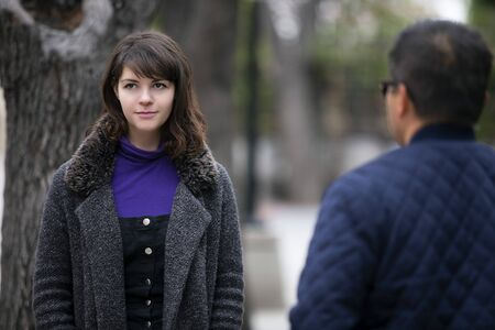 Woman walking outdoors in the city and looking snobby while running into an ex boyfriend or looking annoyed by an insulting stranger.  It also depicts social anxiety. Stok Fotoğraf - 127059324