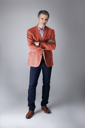 Middle-aged fashion model wearing coral colored sports coat or jacket for the fall clothing collection. Depicts modern colorful apparel style for 2019. Reklamní fotografie