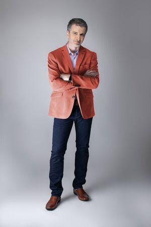 Modella di mezza età che indossa un cappotto o una giacca sportiva color corallo per la collezione di abbigliamento autunnale. Rappresenta lo stile di abbigliamento moderno e colorato per il 2019. Archivio Fotografico