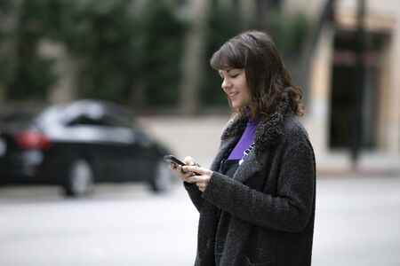 Young female using mobile phone app and waiting for a rideshare or pedestrian tourist checking online map for gps navigation.  Depicts city life and how millennials travel.