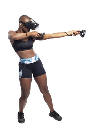 Athletic black female playing a first person shooter video game in VR with a virtual reality headset and controllers. She is pretending to shoot a gun or rifle. Depicts gaming and exercise.