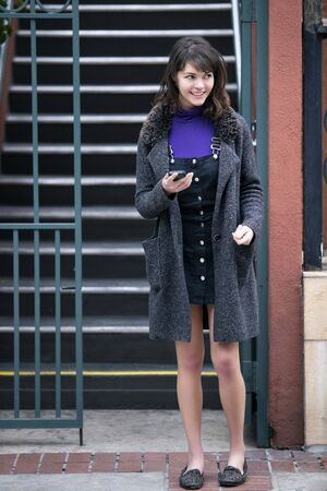 Young female millennial waiting outside apartment home by the stairs for a rideshare or taxi cab.  She is holding her mobile phone and messaging or using app. Stock Photo