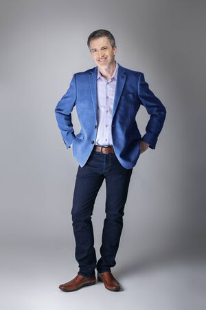Middle-aged Caucasian businessman looking posh wearing modern fall collection style blue jacket.  Depicts confident and mature stylish fashion.  Shot in studio for catalog look. Stockfoto